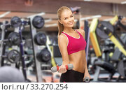 happy young woman with dumbbells exercising in gym. Стоковое фото, фотограф Syda Productions / Фотобанк Лори