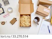 Купить «parcel with straw filler and mug at post office», фото № 33270514, снято 11 января 2019 г. (c) Syda Productions / Фотобанк Лори