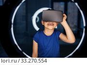 Купить «boy in vr glasses over illumination in dark room», фото № 33270554, снято 14 декабря 2019 г. (c) Syda Productions / Фотобанк Лори