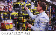 Купить «Male customer choose locksmith tools at hardware store», видеоролик № 33271422, снято 8 апреля 2020 г. (c) Яков Филимонов / Фотобанк Лори