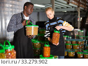 Man and woman stacking plastic buckets with pickled olives. Стоковое фото, фотограф Яков Филимонов / Фотобанк Лори