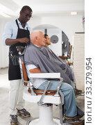 Купить «African barber putting on hairdresser cape to elderly client», фото № 33279954, снято 22 августа 2019 г. (c) Яков Филимонов / Фотобанк Лори