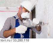 Купить «Constructor in helmet is perforating wall with drill», фото № 33280118, снято 18 мая 2017 г. (c) Яков Филимонов / Фотобанк Лори