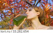 Beautiful girl is drinking green drink, spirulina, chlorella and wheatgrass smoothie outdoors in the park on a tree background with red and orange leaves. Healthy lifestyle, detox. Стоковое видео, видеограф Ольга Балынская / Фотобанк Лори