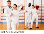 Купить «Woman fencer practicing new movements with trainer at fencing room», фото № 33282958, снято 11 июля 2018 г. (c) Яков Филимонов / Фотобанк Лори