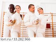 Купить «Smiling fencers posing with foils together at fencing room», фото № 33282966, снято 11 июля 2018 г. (c) Яков Филимонов / Фотобанк Лори