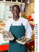 Купить «Salesman offering fresh clams in fish store», фото № 33283034, снято 17 октября 2018 г. (c) Яков Филимонов / Фотобанк Лори