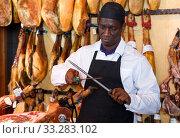 Salesman sharpening knife for cutting ham. Стоковое фото, фотограф Яков Филимонов / Фотобанк Лори