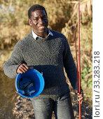 Fisherman holding rod and bucket. Стоковое фото, фотограф Яков Филимонов / Фотобанк Лори