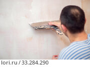 Купить «The process of filling walls. Repair of the living quarters. Interior decoration with putty. Stucco white primer», фото № 33284290, снято 6 июня 2020 г. (c) Екатерина Кузнецова / Фотобанк Лори