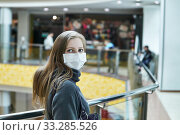 Купить «Young woman in a medical mask in a public space», фото № 33285526, снято 1 марта 2020 г. (c) Евгений Харитонов / Фотобанк Лори