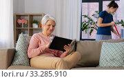 Купить «old woman with tablet pc and housekeeper at home», видеоролик № 33285910, снято 19 января 2020 г. (c) Syda Productions / Фотобанк Лори