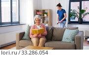 Купить «old woman reading book and housekeeper at home», видеоролик № 33286054, снято 19 января 2020 г. (c) Syda Productions / Фотобанк Лори