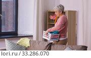 Купить «senior woman picking clothes for laundry at home», видеоролик № 33286070, снято 18 февраля 2020 г. (c) Syda Productions / Фотобанк Лори
