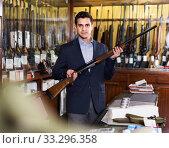 Купить «Handsome adult male in hunting shop with rifle in hands», фото № 33296358, снято 11 декабря 2017 г. (c) Яков Филимонов / Фотобанк Лори