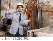 Man in helmet holding paper. Стоковое фото, фотограф Яков Филимонов / Фотобанк Лори