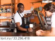 Купить «Young man bartender giving beer with foam to man client», фото № 33296418, снято 28 августа 2019 г. (c) Яков Филимонов / Фотобанк Лори
