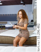 Купить «Young attractive woman choosing right mattress with booklet in home furnishings store», фото № 33296482, снято 22 октября 2018 г. (c) Яков Филимонов / Фотобанк Лори