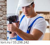 Купить «Repairman working with drilling drill perforator», фото № 33298242, снято 9 декабря 2016 г. (c) Elnur / Фотобанк Лори