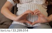 pregnant woman showing hand heart gesture. Стоковое видео, видеограф Syda Productions / Фотобанк Лори