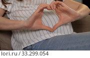 Купить «pregnant woman showing hand heart gesture», видеоролик № 33299054, снято 22 февраля 2020 г. (c) Syda Productions / Фотобанк Лори