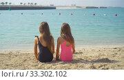 Купить «Little happy funny girls have a lot of fun at tropical beach playing together.», видеоролик № 33302102, снято 3 марта 2020 г. (c) Дмитрий Травников / Фотобанк Лори