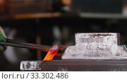 Купить «Blacksmith putting a longer piece of incandescent metal under the pressure of industrial forging machine - the piece falls down on the floor», видеоролик № 33302486, снято 6 июня 2020 г. (c) Константин Шишкин / Фотобанк Лори