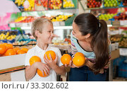 Купить «Portrait of happy woman and her little son choosing oranges at shop», фото № 33302602, снято 20 апреля 2019 г. (c) Яков Филимонов / Фотобанк Лори