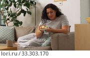 Купить «smiling young woman eating cake at home», видеоролик № 33303170, снято 24 февраля 2020 г. (c) Syda Productions / Фотобанк Лори