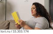 Купить «woman reading book and drinking coffee at home», видеоролик № 33303174, снято 24 февраля 2020 г. (c) Syda Productions / Фотобанк Лори