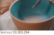 Купить «Pottery - man is painting a clay bowl inside with blue on a pottery wheel», видеоролик № 33303294, снято 5 апреля 2020 г. (c) Константин Шишкин / Фотобанк Лори