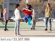 Energetic kids playing and skipping on elastic jumping rope in european yard. Стоковое фото, фотограф Яков Филимонов / Фотобанк Лори