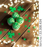 green cupcakes and shamrock on wooden table. Стоковое фото, фотограф Syda Productions / Фотобанк Лори