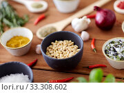Купить «pine nuts in bowl and spices on kitchen table», фото № 33308602, снято 6 сентября 2018 г. (c) Syda Productions / Фотобанк Лори