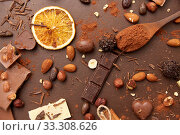 Купить «cocoa beans, chocolate, nuts and cinnamon sticks», фото № 33308626, снято 1 февраля 2019 г. (c) Syda Productions / Фотобанк Лори