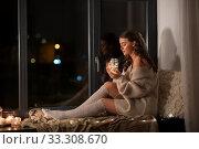 Купить «woman with garland lights in glass mug at home», фото № 33308670, снято 19 января 2020 г. (c) Syda Productions / Фотобанк Лори