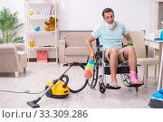 Купить «Young man in wheel-chair cleaning the house», фото № 33309286, снято 29 июля 2019 г. (c) Elnur / Фотобанк Лори