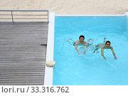 Купить «Upper view of couple swimming in infinity pool», фото № 33316762, снято 8 апреля 2020 г. (c) PantherMedia / Фотобанк Лори