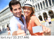 Купить «Cheerful couple showing tourist pass in Piazza San Marco», фото № 33317446, снято 30 марта 2020 г. (c) PantherMedia / Фотобанк Лори