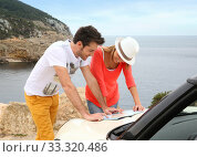 Couple reading map on road trip with cabriolet. Стоковое фото, фотограф Fabrice Michaudeau / PantherMedia / Фотобанк Лори
