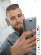 Young man sending text message with smartphone. Стоковое фото, фотограф Fabrice Michaudeau / PantherMedia / Фотобанк Лори