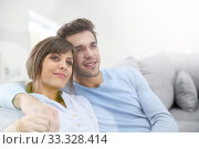 Young couple relaxing in sofa, looking towards the future. Стоковое фото, фотограф Fabrice Michaudeau / PantherMedia / Фотобанк Лори