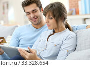 Young couple shopping on internet with tablet. Стоковое фото, фотограф Fabrice Michaudeau / PantherMedia / Фотобанк Лори