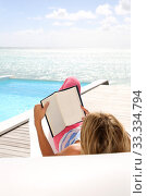 Купить «Rear view of woman reading novel by the sea», фото № 33334794, снято 6 июля 2020 г. (c) PantherMedia / Фотобанк Лори
