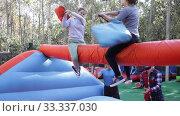 Купить «Female friends having funny wrestling by pillows on inflatable beam in outdoor amusement park», видеоролик № 33337030, снято 12 ноября 2019 г. (c) Яков Филимонов / Фотобанк Лори