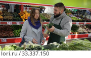 Купить «Smiling male seller assisting customer to buy leek in grocery shop», видеоролик № 33337150, снято 20 ноября 2019 г. (c) Яков Филимонов / Фотобанк Лори