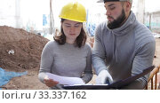 Купить «Two confident engineers discussing blueprint while standing at construction site», видеоролик № 33337162, снято 11 декабря 2019 г. (c) Яков Филимонов / Фотобанк Лори