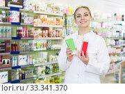 Купить «Female pharmacist standing with medicines in pharmacy», фото № 33341370, снято 26 марта 2018 г. (c) Яков Филимонов / Фотобанк Лори