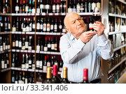 Купить «Elderly man checks the color and taste of red wine in a liquor store», фото № 33341406, снято 5 апреля 2020 г. (c) Яков Филимонов / Фотобанк Лори