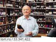 Купить «Elderly man chooses red wine in a liquor store», фото № 33341422, снято 5 апреля 2020 г. (c) Яков Филимонов / Фотобанк Лори